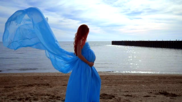 Pregnant woman in blue dress flying on wind. Pregnancy concept