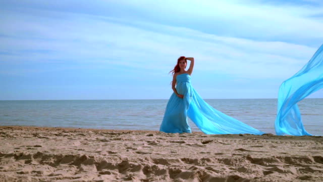 Pregnant woman in blue dress posing on beach. Beach holiday. Romantic woman