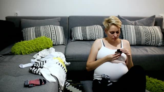 Mujer embarazada busca en ropa de recién nacido de su futuro bebé, la madre buscando su nuevo armario de su bebé - vídeo