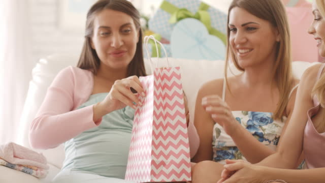 Pregnant woman opening presents on baby shower party video