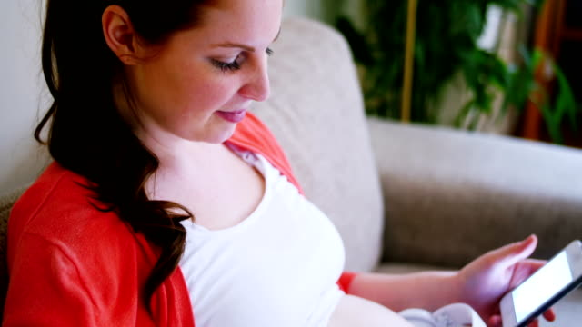 Pregnant woman placing headphones on stomach while using mobile phone video