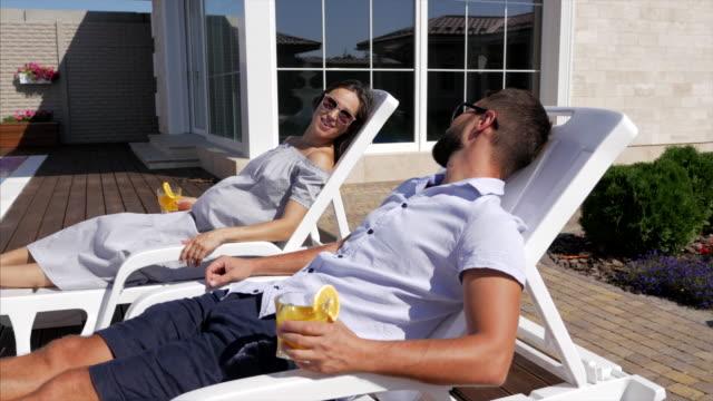 schwangere frau. schwangere frau und ihr mann in der nähe der pools - sun chair stock-videos und b-roll-filmmaterial