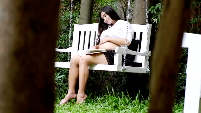 Pregnant woman reading and drink milk in the garden video