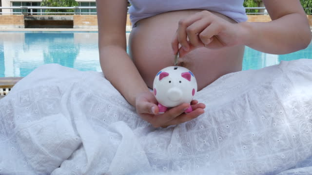 pregnant woman , saving money for her baby concept - porcelain stock videos & royalty-free footage