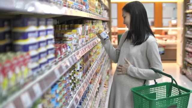 schwangere frau im supermarkt einkaufen - etikett stock-videos und b-roll-filmmaterial