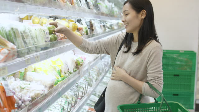 pregnant woman shopping in super market - packaging video stock e b–roll