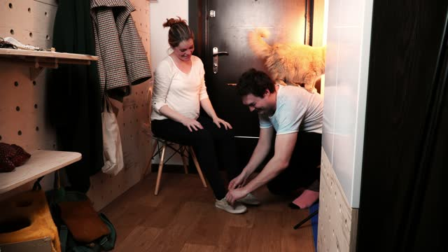 Pregnant woman sits on chair in corridor and man helps her to tie shoelaces
