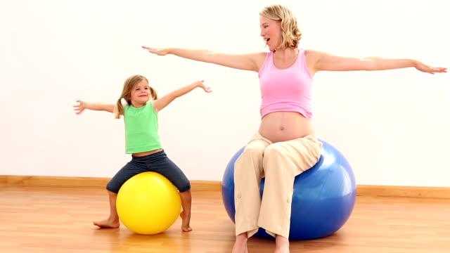 Femme enceinte assise sur un ballon d'exercice avec petite fille - Vidéo