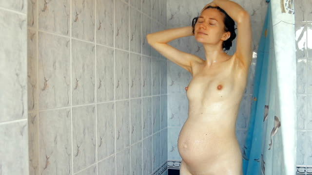 Pregnant woman taking shower Pregnant woman taking showers in bathroom, she washing her hairs seductive women stock videos & royalty-free footage