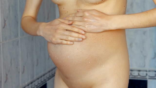 schwangere frau unter dusche - schwanger stock-videos und b-roll-filmmaterial