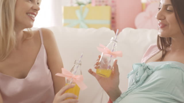 Pregnant woman toasting with friend at baby shower video