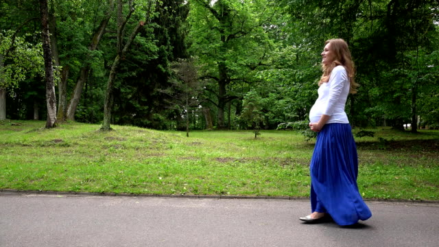pregnant woman walking in park on summer video