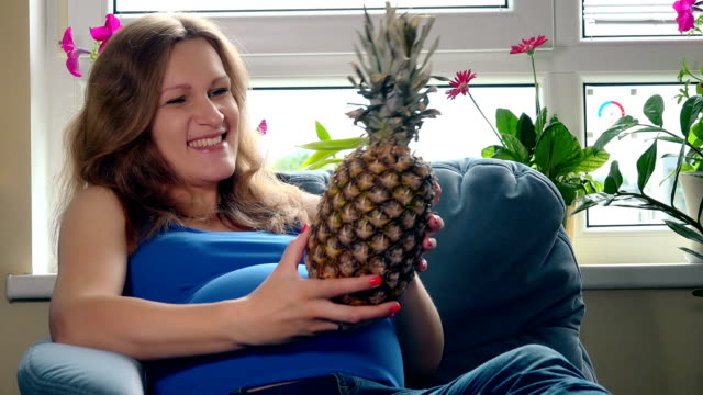 Pregnant woman with big belly holding pineapple ananas fruit sitting on sofa