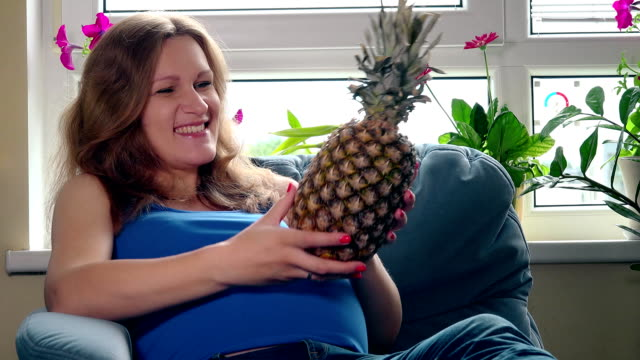 Pregnant woman with big belly holding pineapple ananas fruit sitting on sofa video