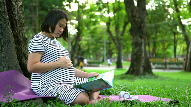 Pregnant woman with book sits in the park and read the book to her baby. video