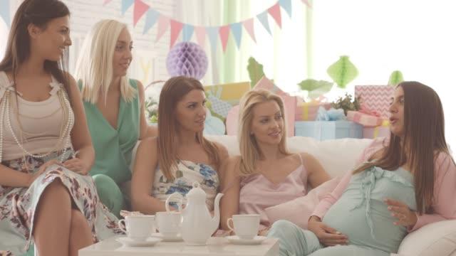 vídeos de stock, filmes e b-roll de mulher grávida com amigos na festa do chuveiro de bebê - chá de bebê