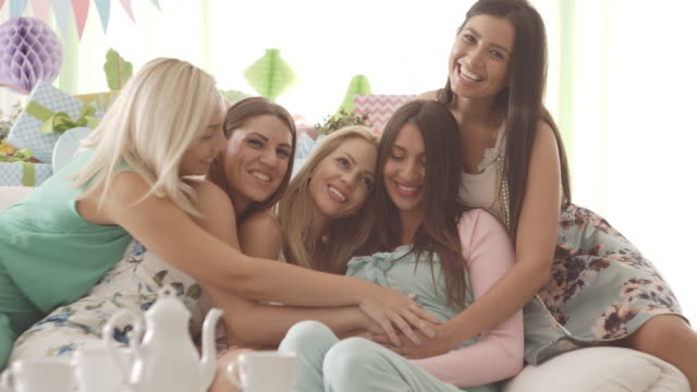 Pregnant woman with friends on baby shower video
