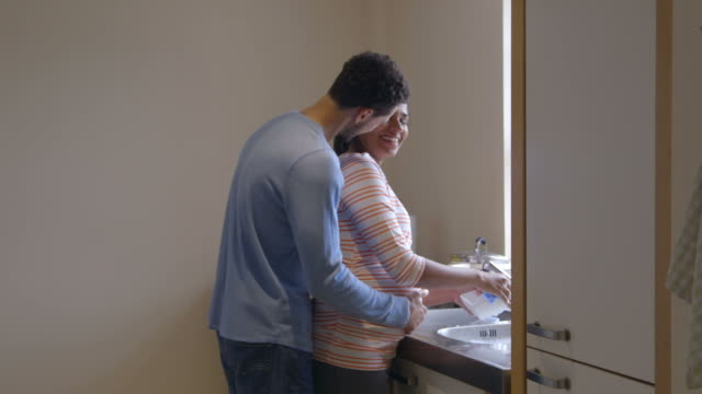 Pregnant Woman With Partner Washing Dishes In Kitchen Sink video