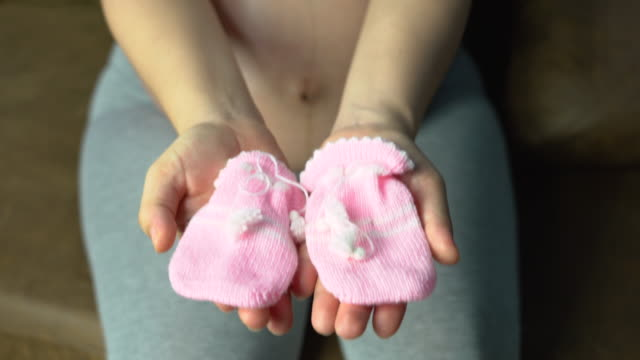 Pregnant women are showing their baby clothes.