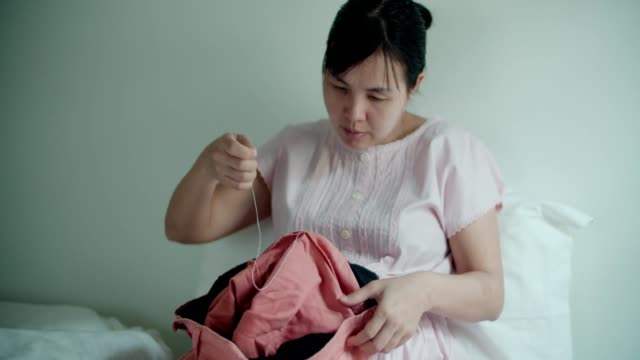 Pregnant women tailor sewing by hand