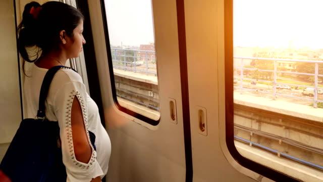 Mulheres gravidas que viajam pelo trem do metro e que olham fora - vídeo