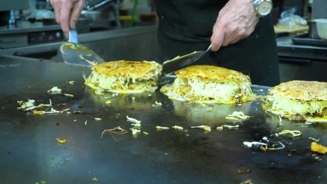 preparation and frying of okonomiyaki - traditional japanese savory pancakes, hiroshima, japan. - hiroshima filmów i materiałów b-roll