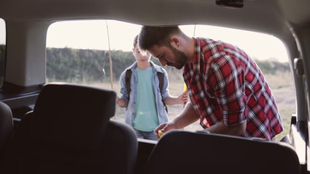Preparation for fishing Father and son preparing fishing equipment in the trunk of a car hobbies stock videos & royalty-free footage