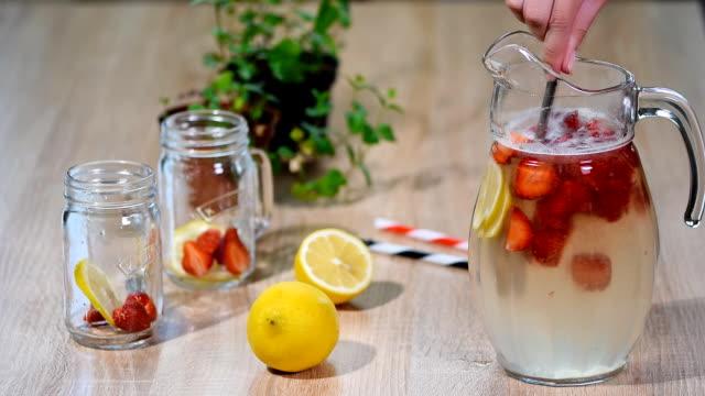 vídeos de stock e filmes b-roll de preparation homemade refreshing strawberry lemonade with mint. - limonada tradicional