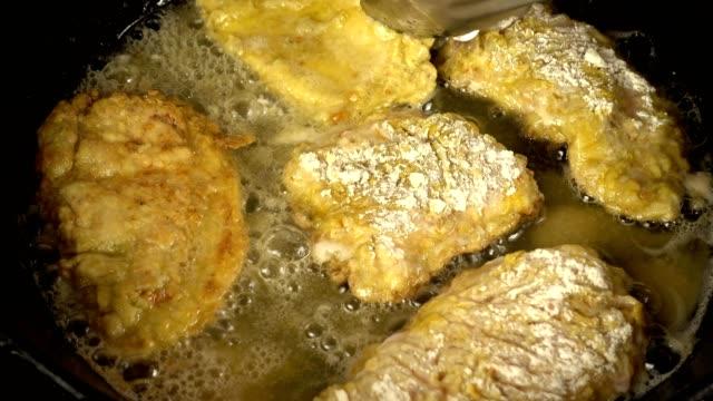 beredning av en kyckling chop på en gjutjärn stekpanna. - frying pan bildbanksvideor och videomaterial från bakom kulisserna
