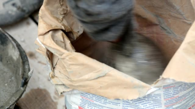 Preparation of building glue in a bucket. Construction worker mixes water with cement. cement stock videos & royalty-free footage