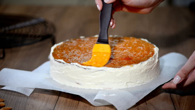 Preparation of cake, spreading of apricot jam on cakes video