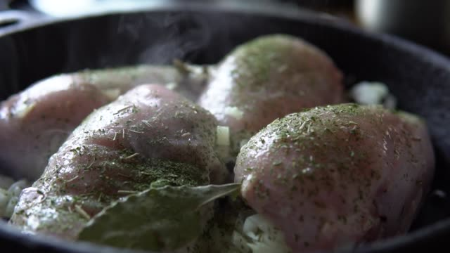 Preparation of chicken with spices in a frying pan. Someone sprinkles meat with seasonings, slow motion. Close-up of cooking chicken with parsley, dill, bay leaf, onion in a frying pan. fillet stock videos & royalty-free footage