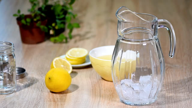 Preparation of lemonade from lemon and mint in a glass bottle in a light kitchen. video