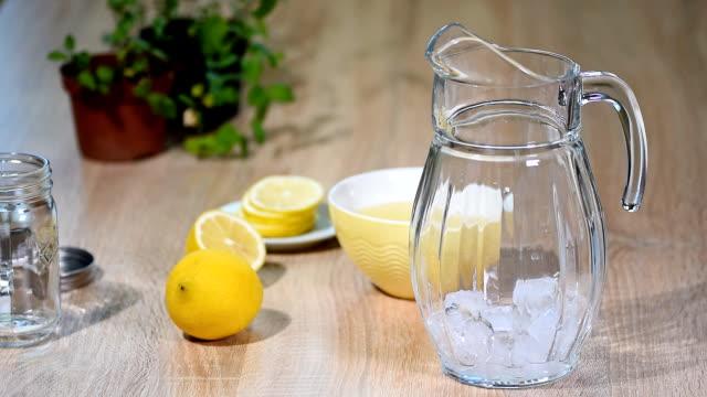 vídeos de stock e filmes b-roll de preparation of lemonade from lemon and mint in a glass bottle in a light kitchen. - limonada tradicional