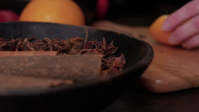 Preparation of mulled wine. Female hands cut orange on wooden cutting board. Anise stars and cinnamon sticks in brown wooden bowl in foreground. Close up slider shot.