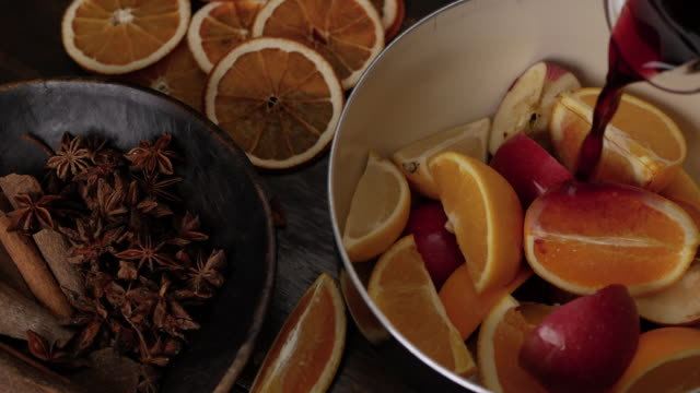 Preparation of mulled wine. Pour red wine in to saucepan on top of lemons, oranges, apples. Anise stars and cinnamon sticks in brown wooden bowl in foreground. Close up top view.