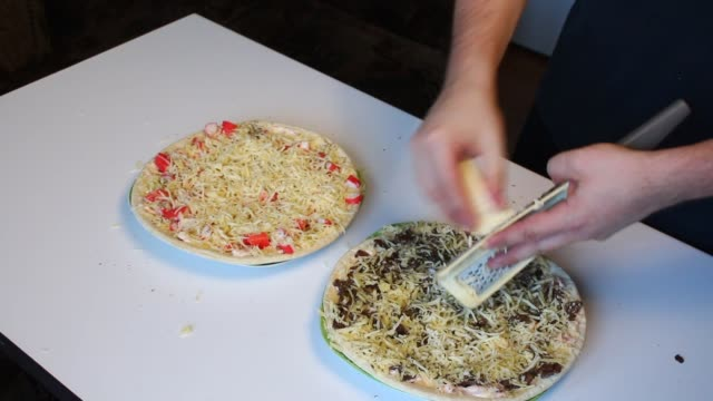 Preparation of pizza. The man adjusts the pizza with mushrooms on the table. video