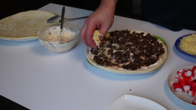 Preparation of pizza. The man covers the base for pizza with mushrooms a thick layer of cheese. Next to the table are other ingredients. video