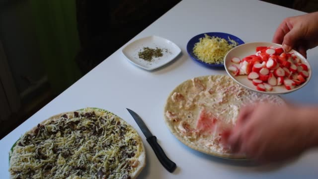 Preparation of pizza. The man piles a mixture of crushed crab sticks on the pizza. Next to the table is a pizza, ready for cooking and other ingredients. video