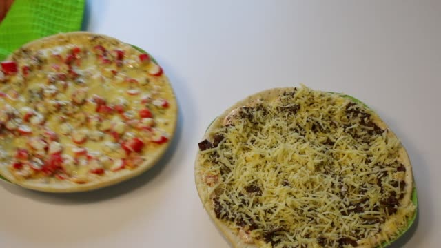 Preparation of pizza. The man puts on the table a ready pizza with crab sticks and picks up a pizza parcel with mushrooms. video