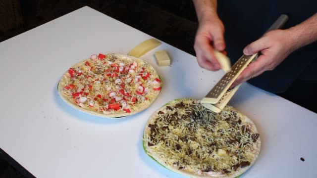 Preparation of pizza. The man rubs cheese on a grater on a pizza with crab sticks and mushrooms. video