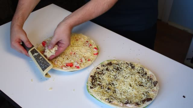 Preparation of pizza. The man rubs cheese on a grater on a pizza with crab sticks and leaves. video