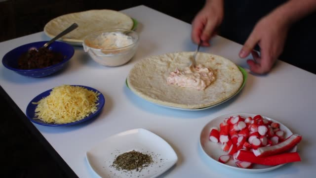 Preparation of pizza. The man smears a mixture of mayonnaise and crushed tomatoes on the basis for pizza. Next to the table are other ingredients. video