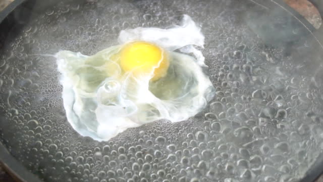 Preparation of poached egg on bonfire. video