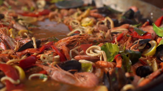 Preparation of seafood and noodle soup close-up. Tracking shot in slow motion