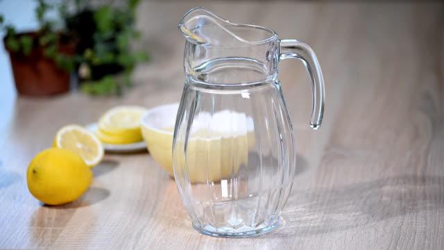 beredning av lemonad drycken. lemonad i kannan och citroner med mynta på bordet - konserveringsburk bildbanksvideor och videomaterial från bakom kulisserna