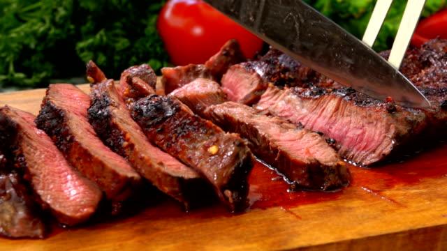 vídeos de stock, filmes e b-roll de bife de carne preparado cortado em fatias com uma faca em uma tábua de madeira - bife