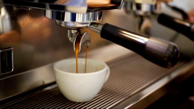 prepares espresso in coffee shop with white cup.