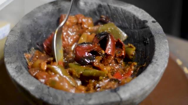zubereitung eines gemischten molcajete, mexikanische küche, geröstete tomaten mit knoblauch und chili in vulkanischem stein serviert. traditionelles essen. chef bewegt zutaten mit löffel - chilli stock-videos und b-roll-filmmaterial