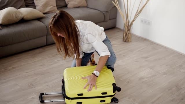 Vorbereitung Tasche für die Reise. Junge Frau packt und verzweifelt versucht, vollen Koffer zu schließen und schließt einen Reißverschluss darauf, während sie auf dem Boden im Wohnzimmer sitzt. Zeitlupe – Video